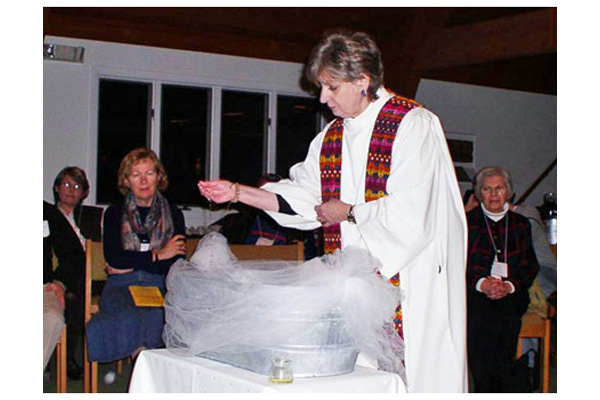ECDNE Priest Jean Marchant at a Baptism